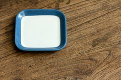 Empty square white and blue color dish on wood Stock Photo