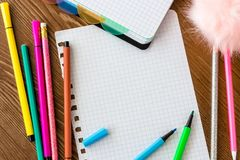 Empty squared page with open felt tip pens. On wooden desk stock photography
