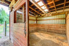 Empty stable in wooden horse barn. Royalty Free Stock Image