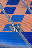 Empty stadium seats. Rows of empty stadium seats and aisles in blue and orange Royalty Free Stock Photography