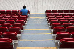 Empty stadium seats with a man alone. Empty red stadium seats with a man alone Royalty Free Stock Photo