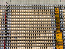 Empty stadium tribunes. Empty yellow seats at soccer stadium between footsteps Stock Photography