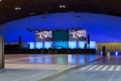 Empty Stage with Blue Lights, Black Ceiling and Multiple Screen Display. Rimini, Italy - june 2018: Empty Stage with Blue Lights, Black Ceiling and Multiple stock photo