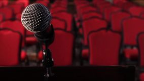 On an empty stage microphone in front of an empty hall. Scene. Microphone on stage close-up.  stock video footage