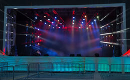 Empty stage. With smoke and soffits. Light rays pass through the smoke. Barriers are in the foreground Stock Image