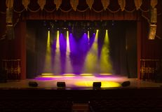 An empty stage of the theater, lit by spotlights and smoke Royalty Free Stock Photo