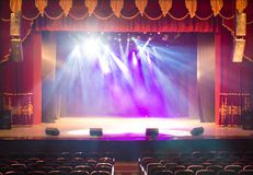 An empty stage of the theater, lit by spotlights and smoke Stock Photography