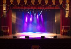 An empty stage of the theater, lit by spotlights and smoke Stock Photos