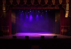 An empty stage of the theater, lit by spotlights and smoke Stock Images