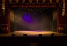 An empty stage of the theater, lit by spotlights and smoke Royalty Free Stock Image