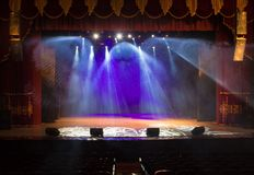 An empty stage of the theater, lit by spotlights and smoke Royalty Free Stock Photos