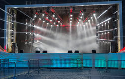 Empty stage with white lights. Empty stage with smoke and soffits. White light rays pass through the smoke. Barriers are in the foreground royalty free stock photo