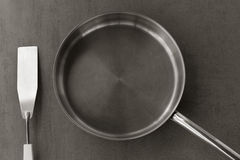 Empty stainless steel frying pan and spatula overhead view on the gray background, black white photos. Used clean empty stainless steel frying pan and spatula Royalty Free Stock Photos