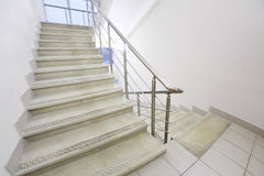 Empty staircase with metal railings. Empty light and simple staircase with metal railings and white walls Royalty Free Stock Photo