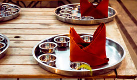 Empty steel plate for indian cusine. Empty steel plate with red napkin on wooden table for serving indian food or cusine. The plate and multiple bowls are for stock photos