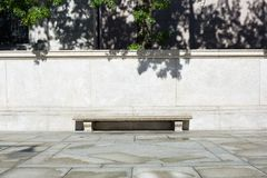Empty stone bench with light stone background and tree leaves shadows. In a sunny day Stock Image