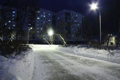 Empty stone causeway, residential building and white snow Stock Photos