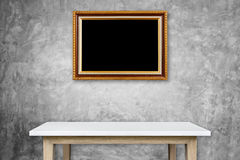 Empty stone table and gold vintage wooden photo frame hang on th Royalty Free Stock Images