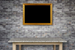 Empty stone table and gold vintage wooden photo frame hang on th Royalty Free Stock Photography