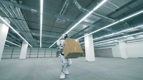 Empty storage unit with a robot lifting a carton box and carrying it. 4K stock video footage