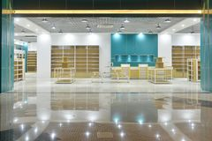 Empty store front in modern commercial shopping mall. Empty store front,Led lamps are installed on shop square shape ceiling in commercial building Stock Photo