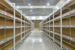 Empty shelves of supermarket interior. Empty store interior,Led lamps are installed on shop square shape ceiling ,empty shelves stock photography
