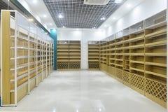 Empty store shelves of supermarket interior. Empty store interior,Led lamps are installed on shop square shape ceiling ,empty shelves stock photos