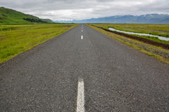 Empty straight asphalt road with view to mountains Stock Photos