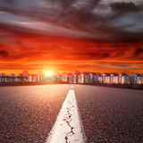 Empty straight road. Entry into the downtown at sunset Royalty Free Stock Photos