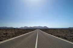 Empty and straight road through the lava fields. On the Canary Islands, Lanzarote, Montanas del Fuego, Spain royalty free stock image