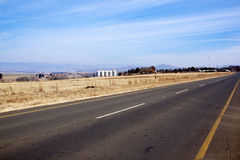 Empty Straight Rural Asphalt Road with Storage Silos. Winter landscape of empty straight rura asphalt road with storage silos against blue sky in South Africa Stock Photography