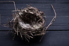 Empty straw nest with twigs on a wooden background. Royalty Free Stock Photos