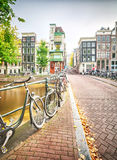 An empty street in Amsterdam. The Netherlands with typical houses and many bicycles parked on the side of a bridge which crosses over a canal Stock Photography