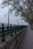 Empty street with bare trees and railways in perspective with river view. Transport and travel concept. Europe lanscape and cityscape. Cold day for journey Royalty Free Stock Photos
