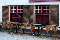 Empty street cafe in european old town. Empty tables and chairs against old white brick building with open shutters and red window Royalty Free Stock Photo