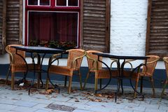 Empty street cafe in european old town. Empty tables and chairs against old white brick building with open shutters and red window Stock Photos