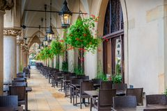 Empty street cafe, located in the arch of shopping arcades in th. E center of Krakow in the square in the morning Royalty Free Stock Image