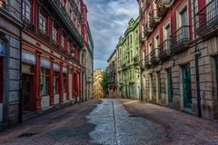 Empty street with colorful old buildings during early morning un. Der cloudy skies Royalty Free Stock Image