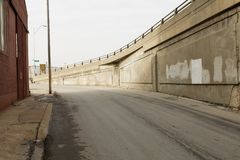 Empty street by concrete bridge stock photos