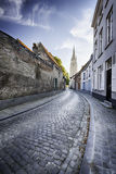 An empty street leading to a church tower Royalty Free Stock Photo