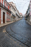 Empty street in Lisbon, Portugal. Empty streets with tram rails and overhead lines in daytime in Lisbon, Portugal royalty free stock image
