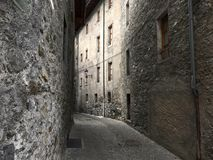 Empty street with stone houses in the historic old village in Bormio, Italy Stock Images