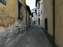 Empty street with stone houses in the historic old village in Bormio, Italy Royalty Free Stock Image