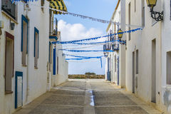 Empty street of white houses with nice blue decoration in Tabarca island during holidays. The photo shows an empty street of white houses with pretty blue and Stock Images