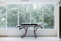 Empty stretcher in a hospital by glass windows, no people Stock Image