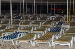 Empty striped loungers by the sea in the evening.  stock image