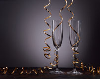 Empty stylish champagne flutes with gold ribbon Stock Images