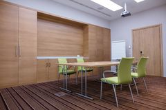 Empty stylish meeting room equipped with video projector. The room has table with sheets of paper on the table, chairs, door, cabinet, flipchart and brown stock photography