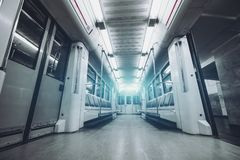 Empty subway train. Wide-angle view from bottom of empty modern underground train car interior with doors opened: empty seats, rows of lamps following to Stock Photos