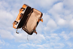 Empty suitcase in mid-air. Empty suitcase with open lid  in mid-air flying past with background of blue sky and cloud Royalty Free Stock Photo
